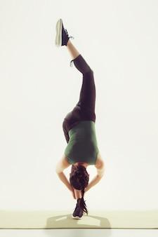 Piękna młoda szczupła kobieta robi ćwiczenia rozciągające na siłowni przed białym