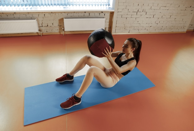 Piękna młoda szczupła kobieta robi jakieś gimnastyki na siłowni z medball. sportowiec, sport, liny, trening, trening, ćwiczenia i koncepcja zdrowego stylu życia