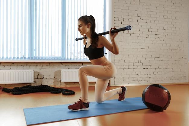 Piękna młoda szczupła kobieta robi jakieś gimnastyki na siłowni