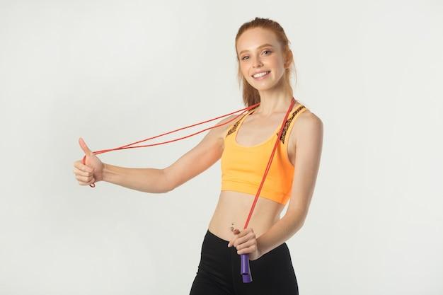 Piękna młoda szczupła kobieta z rudymi włosami w odzieży sportowej z skakanką w rękach