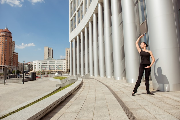 Piękna młoda szczupła, zgrabna baletnica tańczy w pobliżu budynku