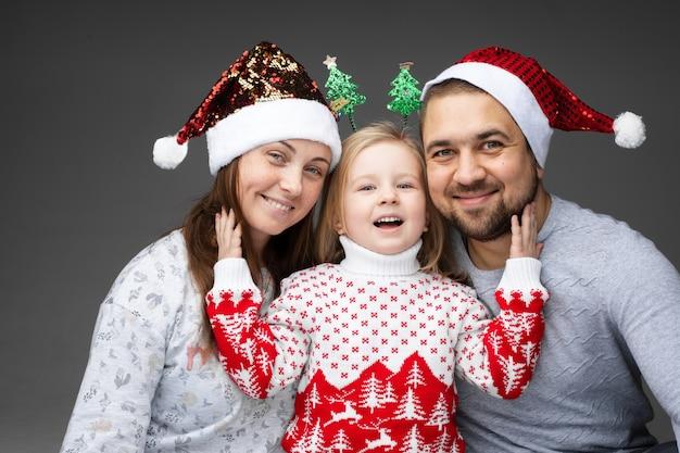 Piękna młoda trzyosobowa rodzina kaukaska spędza razem boże narodzenie