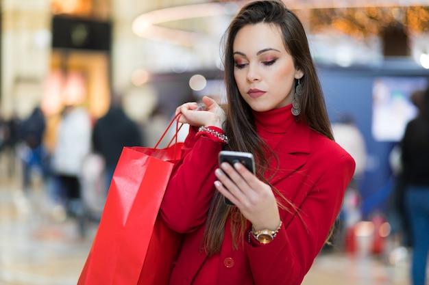 Piękna młoda turystyczna dziewczyna robi zakupy w mediolan w mediolan podczas gdy używać smartphone