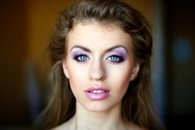 Piękna młoda twarz kobiety z stylu życia wielokolorowe makijaż jasny moda. duże niebieskie oczy