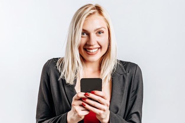 Piękna młoda urocza dziewczyna uśmiecha się i trzyma telefon na szarym tle na białym tle