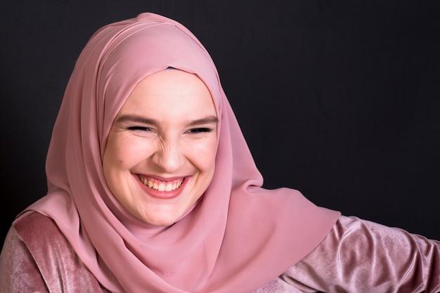 Piękna młoda uśmiechnięta arabska kobieta patrzeje kamerę