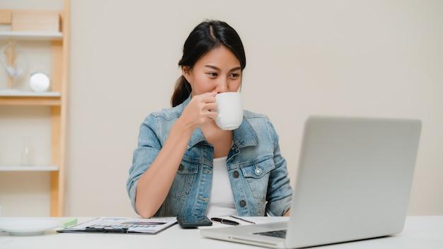 Piękna młoda uśmiechnięta azjatykcia kobieta pracuje na laptopie i pije kawę w żywym pokoju w domu.