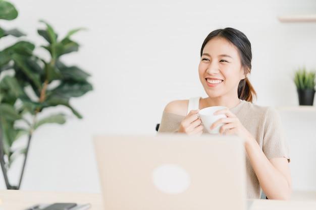 Piękna młoda uśmiechnięta azjatykcia kobieta pracuje na laptopie i pije kawę