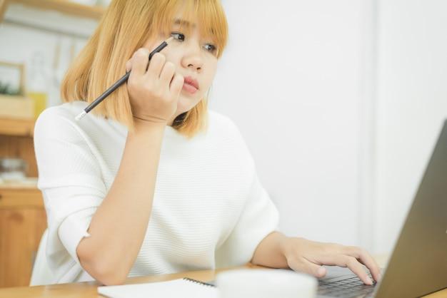 Piękna młoda uśmiechnięta azjatykcia kobieta pracuje na laptopie podczas gdy siedzący w żywym pokoju w domu