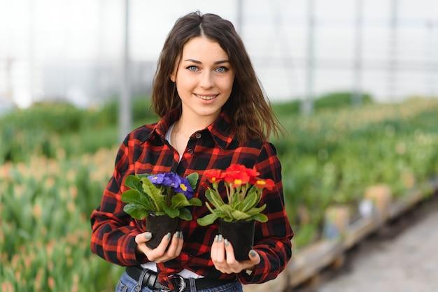 Piękna młoda uśmiechnięta dziewczyna, pracownik z kwiatami w szklarni. skopiuj miejsce, ogród tulipanów