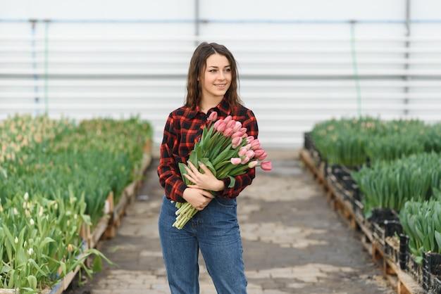 Piękna młoda uśmiechnięta dziewczyna, pracownik z kwiatami w szklarni. tulipany, pudełko z kwiatami. skopiuj miejsce.