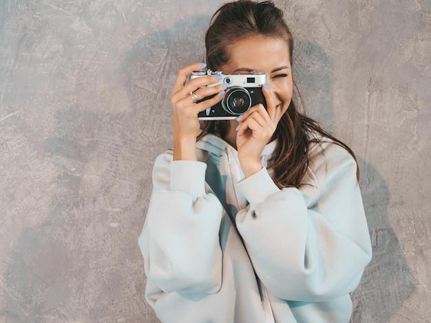 Piękna młoda uśmiechnięta fotograf dziewczyna bierze fotografie używać jej retro kamerę. kobieta robi zdjęcia. model ubrany w swobodną letnią bluzę z kapturem. pozowanie w studio w pobliżu szarej ściany