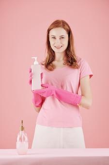 Piękna młoda uśmiechnięta gospodyni domowa w różowych gumowych rękawiczkach pokazująca butelkę nowego detergentu do czyszczenia