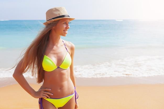 Piękna młoda uśmiechnięta kaukaska dziewczyna w bikini kostium kąpielowy stojąca na tropikalnej plaży z białym piaskiem
