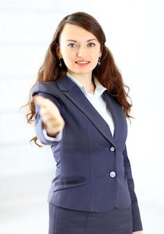 Piękna młoda uśmiechnięta kobieta biznesu, szczęśliwa i uśmiechnięta, z otwartą ręką gotowa do przypieczętowania transakcji lub witania. na białym tle na białym tle.
