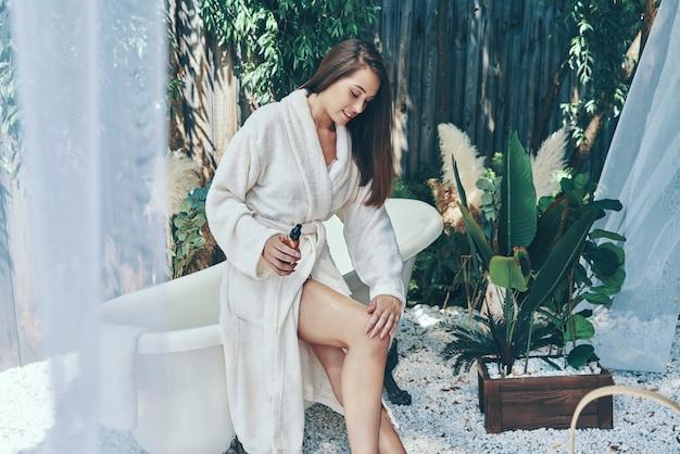 Piękna młoda uśmiechnięta kobieta krem nawilżający opierając się na wannie na zewnątrz