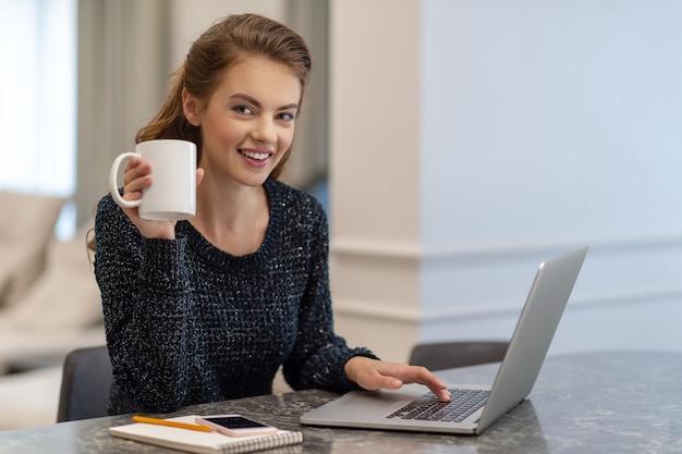 Piękna młoda uśmiechnięta kobieta pracuje na laptopie i pije kawę siedząc w domu