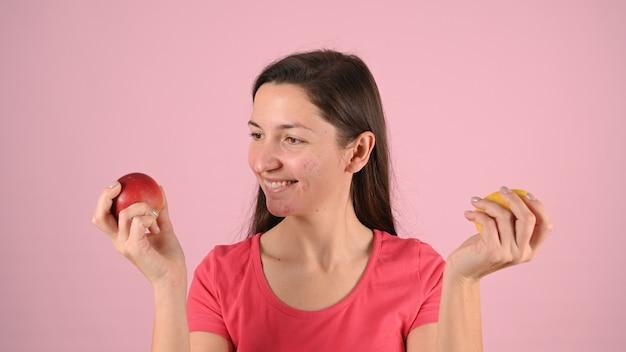 Piękna młoda uśmiechnięta kobieta trzyma jabłko i cytrynę w dłoniach.