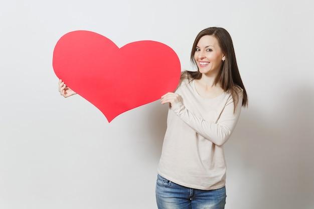 Piękna młoda uśmiechnięta kobieta trzyma wielkie czerwone serce w rękach na białym tle. skopiuj miejsce na reklamę. z miejscem na tekst. koncepcja dzień świętego walentego lub międzynarodowy dzień kobiet.