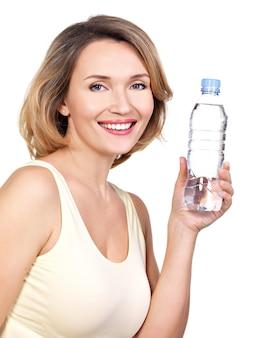 Piękna młoda uśmiechnięta kobieta z butelką wody na białym tle.