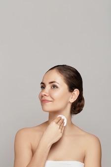 Piękna młoda uśmiechnięta kobieta z czystymi bawełnianymi podkładkami. zabieg na twarz. kosmetologia, uroda i spa .piękna pielęgnacja skóry twarzy famale. ekspresyjne wyrazy twarzy.