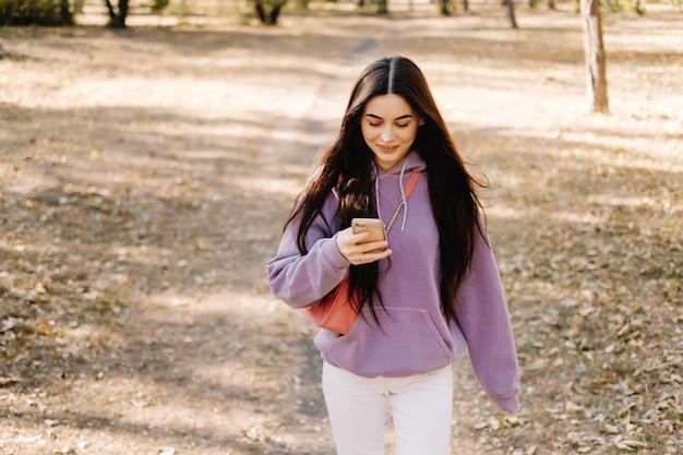 Piękna młoda uśmiechnięta kobieta za pomocą smartfona i spacery w parku jesień.