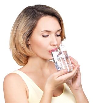 Piękna młoda uśmiechnięta kobieta ze szklanką wody na białej ścianie