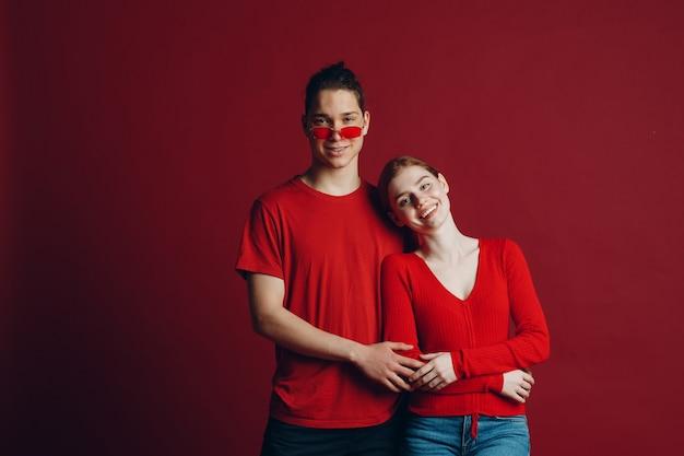 Piękna młoda uśmiechnięta para przytulanie na czerwonym tle. koncepcja walentynki.