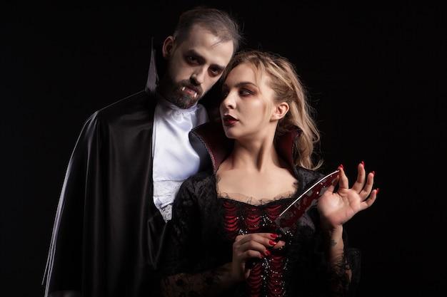 Piękna młoda wampirzyca z ostrzem pokrytym krwią, patrząc na swojego mężczyznę przebranego jak dracula na halloween. uwodzicielska para.