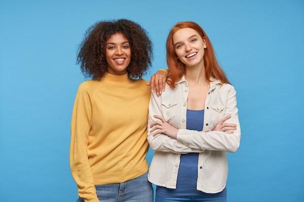 Piękna młoda wesoła długowłosa rudowłosa kobieta trzyma ręce złożone i uśmiecha się przyjemnie, pozując na niebieskiej ścianie ze swoim radosnym przyjacielem o kręconej ciemnej karnacji