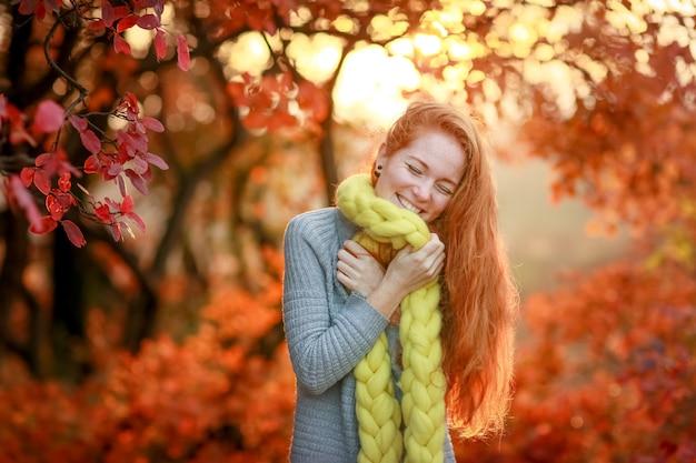 Piękna młoda wesoła kobieta stoi w lesie na tle czerwonych drzew jesienią