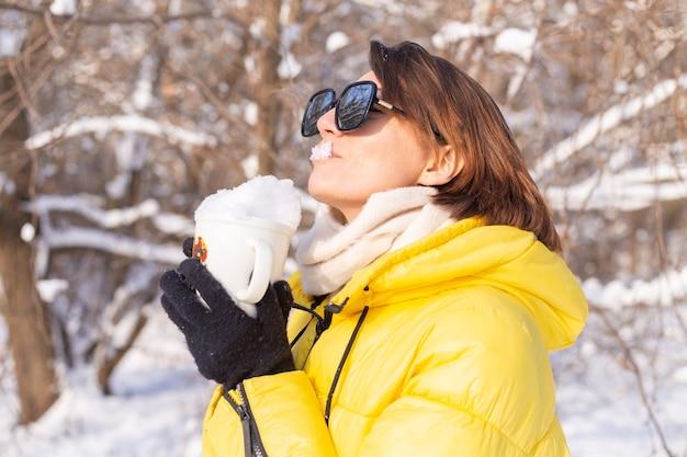 Piękna młoda wesoła kobieta w lesie zimą śnieżny krajobraz w okularach przeciwsłonecznych z kubkiem wypełnionym śniegiem, zabawy