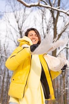 Piękna młoda wesoła kobieta w śnieżnym krajobrazie zimowym lesie raduje się zimą i śniegiem w ciepłych ubraniach
