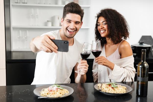 Piękna młoda wieloetniczna para na romantycznej kolacji w domu, popijając czerwone wino i jedząc makaron, tosty, robiąc selfie