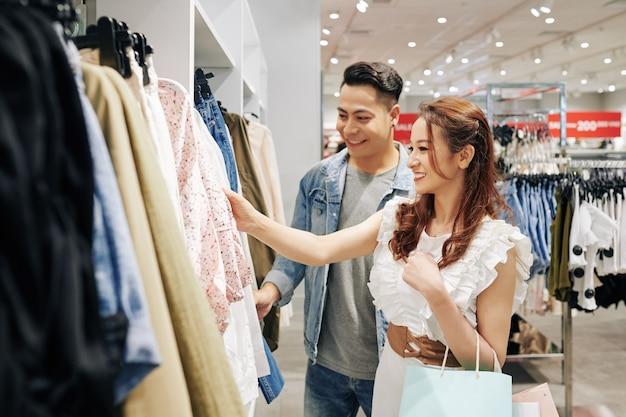 Piękna młoda wietnamka robi zakupy w centrum handlowym ze swoim chłopakiem i patrząc na bluzkę na wieszaku
