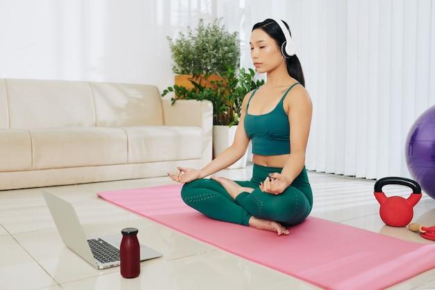 Piękna młoda wietnamka w słuchawkach podczas medytacji przed laptopem w domu