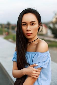 Piękna młoda wietnamska dziewczyna z długą fryzurą w niebieskiej bluzce z odkrytymi ramionami w letni dzień