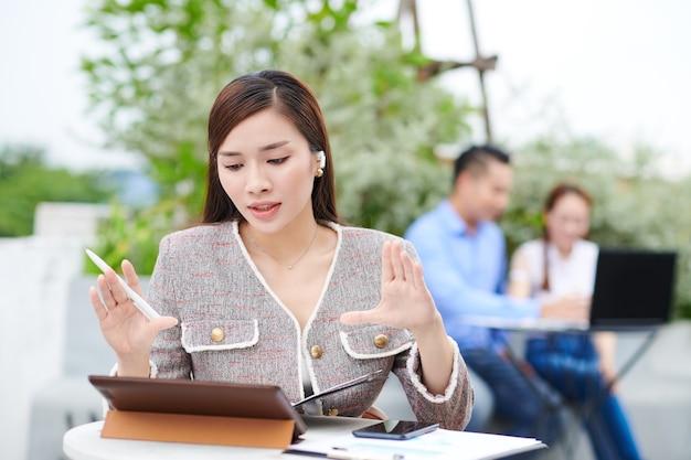 Piękna młoda wietnamska przedsiębiorczyni siedzi przy kawiarnianym stoliku i aktywnie gestykuluje podczas rozmowy wideo ze swoim zespołem