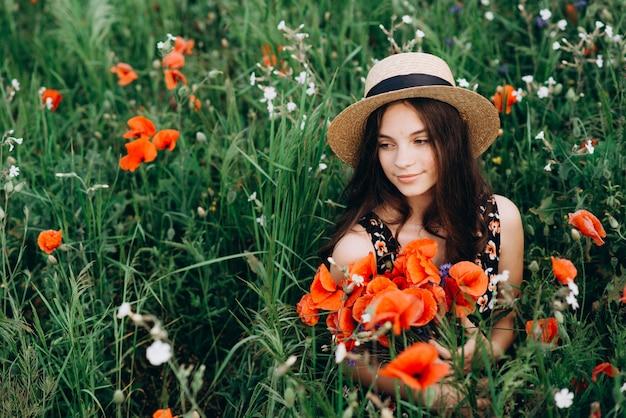 Piękna młoda wolna dziewczyna w kapeluszu w polu letnich czerwonych maków z bukietem