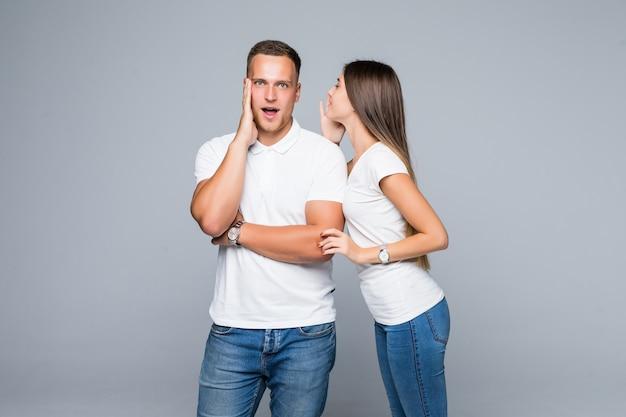 Piękna młoda zaskoczona para w białych koszulkach i dżinsach o tajnej rozmowie