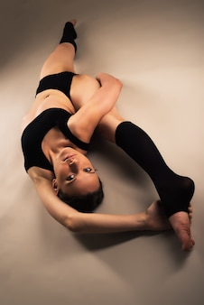 Piękna młoda zdrowa dziewczyna w odzieży sportowej robi trening dla stawów nóg, siedząc na podłodze w ciemnym oświetleniu. pojęcie zdrowego stylu życia.