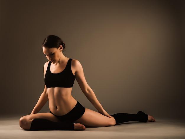 Piękna młoda zdrowa dziewczyna w odzieży sportowej robi trening dla stawów nóg, siedząc na podłodze w studio w ciemnym oświetleniu
