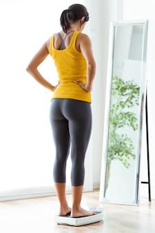 Piękna młoda zdrowa kobieta na domu waży.