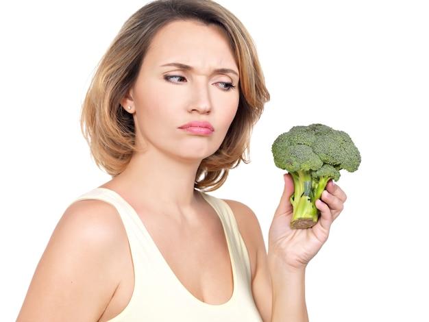 Piękna młoda zdrowa kobieta trzyma brokuły na białym tle.