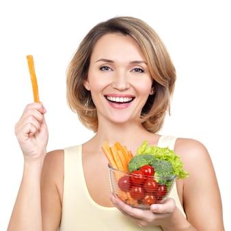 Piękna młoda zdrowa kobieta z talerzem warzyw na białym tle.
