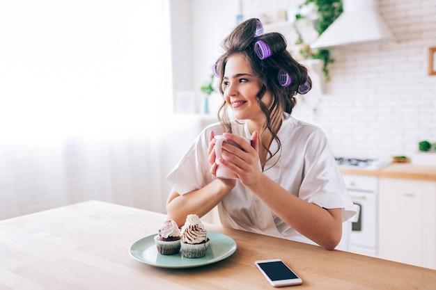 Piękna młoda żeńska gospodyni domowa w kuchni. trzymając kubek i spójrz w bok. uśmiecha się sam. naleśniki i telefon na stole. beztroska młoda kobieta żyjąca pięknym życiem. bez pracy