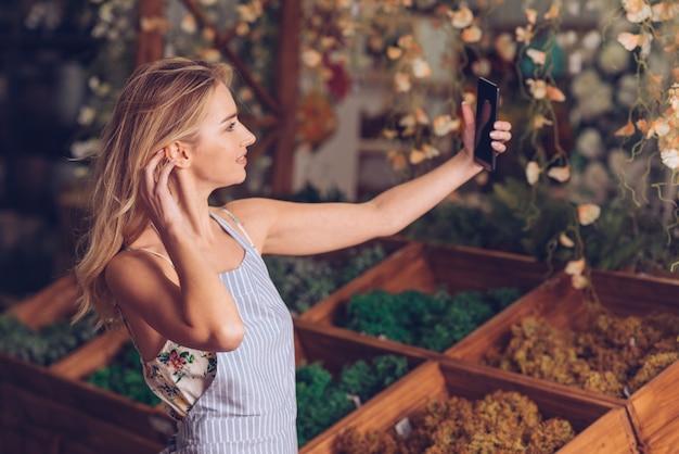 Piękna młoda żeńska kwiaciarnia bierze selfie na telefonie komórkowym w sklepie
