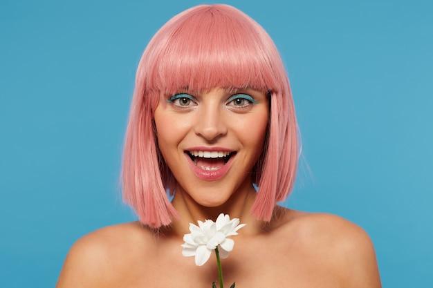 Piękna młoda zielonooka różowowłosa dama z świątecznym makijażem, wyglądająca wesoło z szerokim uśmiechem i trzymająca biały kwiat