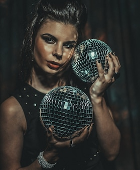 Piękna młoda zmysłowa kobieta trzyma kule dyskotekowe