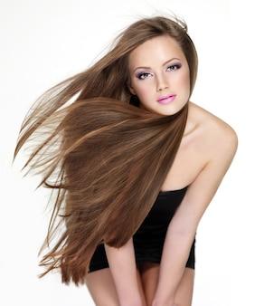 Piękna młoda zmysłowa kobieta z długimi prostymi włosami na białym tle